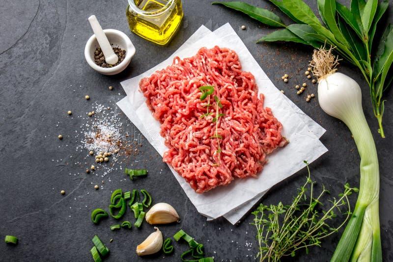 mince Gehakt met ingrediënten voor het koken op zwarte achtergrond Fijngehakt rundvleesvlees Hoogste mening stock foto's