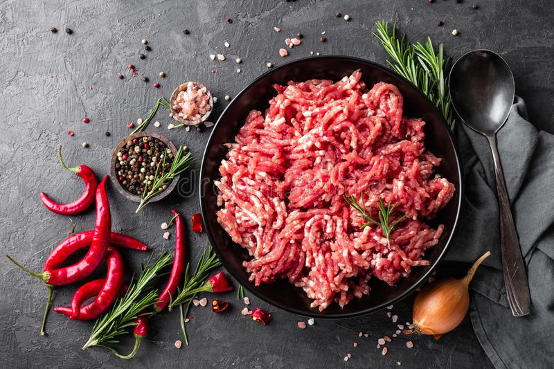 Mince. Ground meat with ingredients for cooking on black background. Top view stock photos
