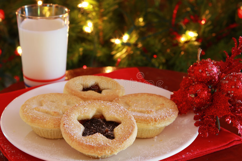 Mince Pies. With a glass of milk, with Christmas tree behind. Santa's treats, waiting for his arrival royalty free stock photography