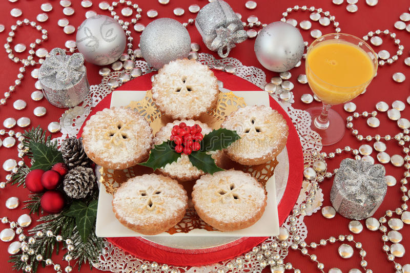 Mince Pies and Egg Nog. Christmas mince pie cakes with egg nog drink, silver bauble decorations, holly and winter greenery on red background stock images