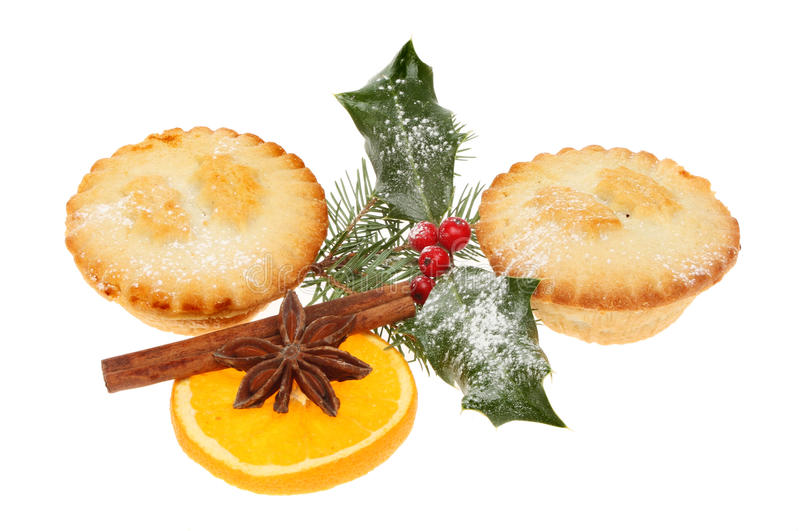 Mince pies and holly. Christmas mince pies decorated with holly, pine needles, orange and spices isolated against white stock photography