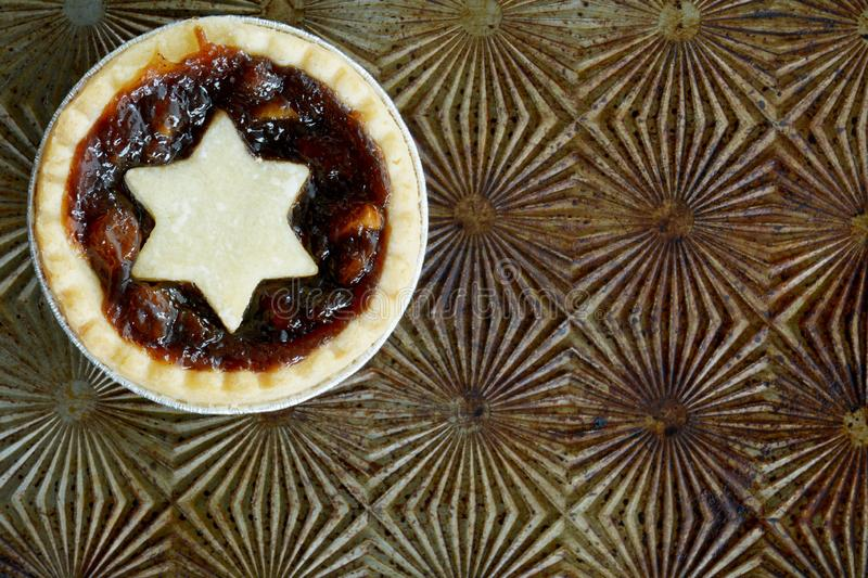 Mince tart on vintage sheet. Traditional Christmas mince tart on vintage baking sheet. Shot from overhead in horizontal format in natural light. Room for text stock images
