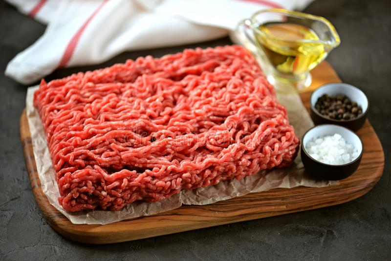 Minced beef meat with sea salt, pepper on a black background. royalty free stock photos