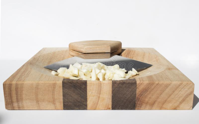 Alaskin Ulu with Minced Garlic. Alaska Ulu Knife Set-Curved Knife with Wood Handle plus Chopping Board with Bowl with minced garlic head on stock images
