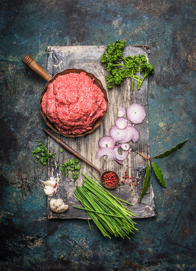 Minced meat in frying pan with cooking ingredients and wooden spoon on dark rustic background royalty free stock photo