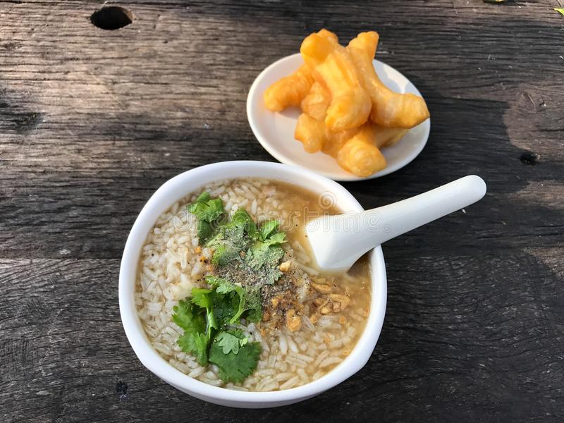 Minced pork congee with deep fried garlic and vegetable in white bowl. Serve with deep fried dough stick. royalty free stock photography