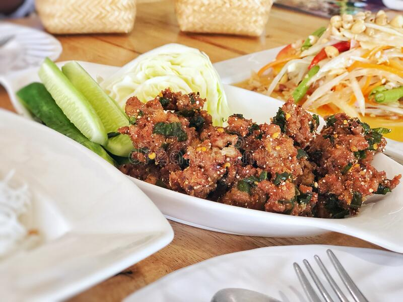 Minced pork spicy salad fried eat with sticky rice and vegetables, serve with Thai papaya salad, famous traditional food Thailand. stock photography