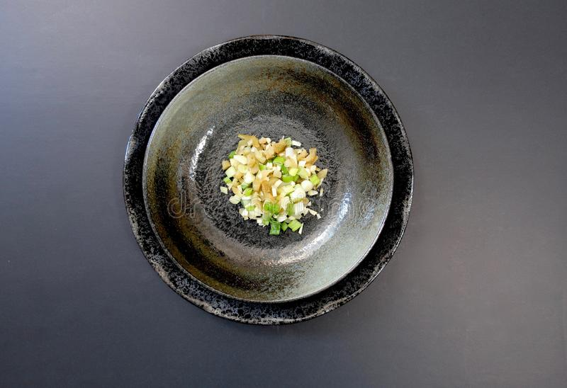 Minced scallion, shallots, and ginger in a black bowl set on a black background royalty free stock images