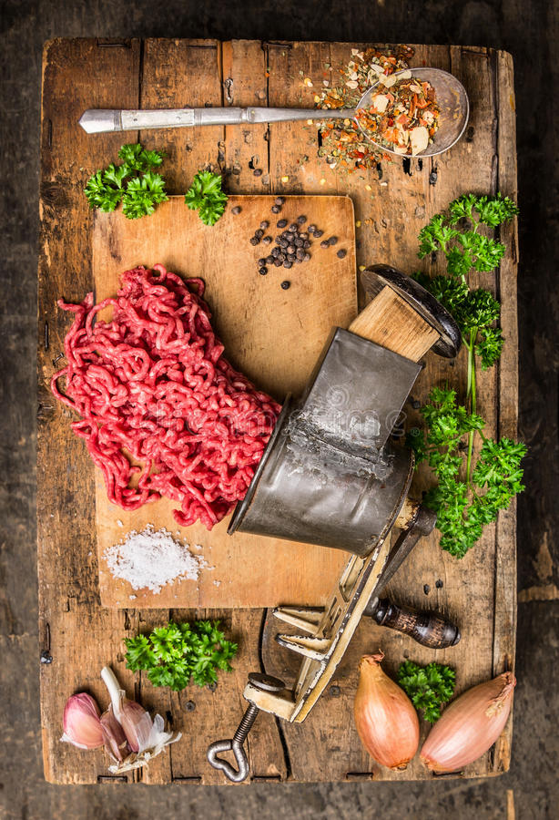 Mincemeat of vintage meat grinder on old wooden table with herbs and spices in spoon stock images