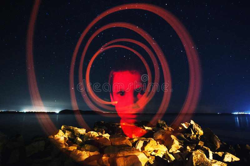 The mind of a child. Conceptual portrait of a thoughtful boy at night. Single image shot using lightpainting stock photo