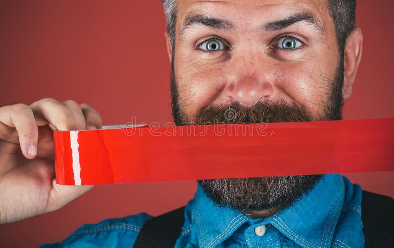 Mind control and propaganda. censorship. Brutal bearded male. man wrapping mouth by adhesive tape. International Human. Right day. Concept freedom of speech and stock images