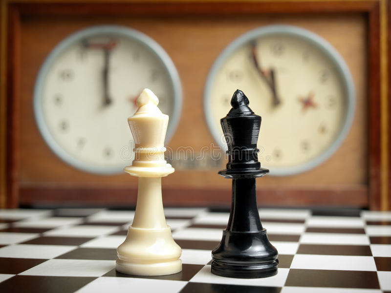 Mind game. White and black king on the chessboard opposing eachother,old chess clock in the background,can be used as concept for conflict,meeting,agreement stock photography