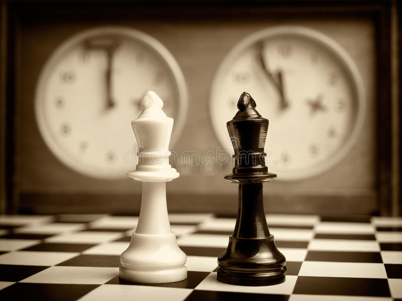Mind game. White and black king on the chessboard opposing eachother,old chess clock in the background,sepia toned,can be used as concept for conflict,meeting royalty free stock photo