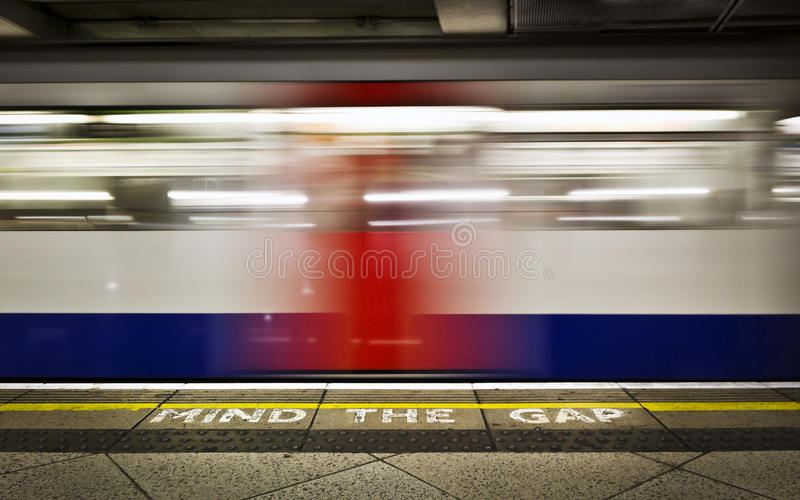 MIND THE GAP. London tube platform edge. Painted warning on the floor. Train passing by stock photography