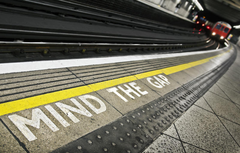 Mind the gap. London tube platform edge. Painted warning on the floor. Train approaching royalty free stock photos