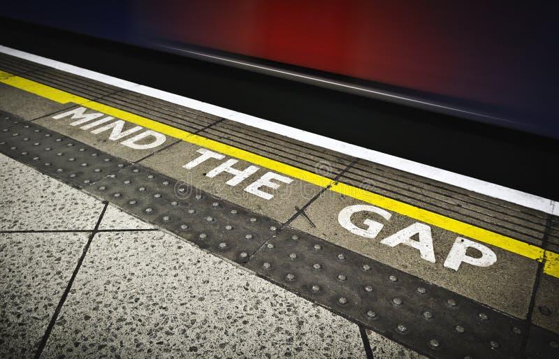 Mind the gap. London tube platform edge. Painted warning on the floor stock images