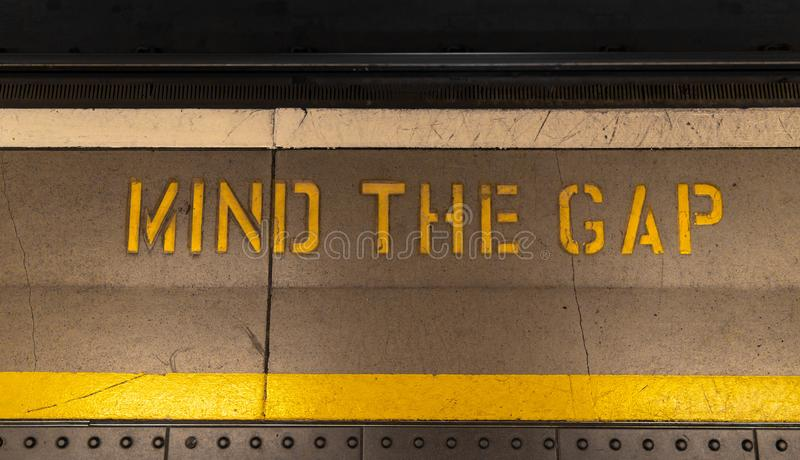 Mind the gap typical sign painted on a tube platform edge. Painted warning on the floor. Mind the gap sign in train station royalty free stock photos