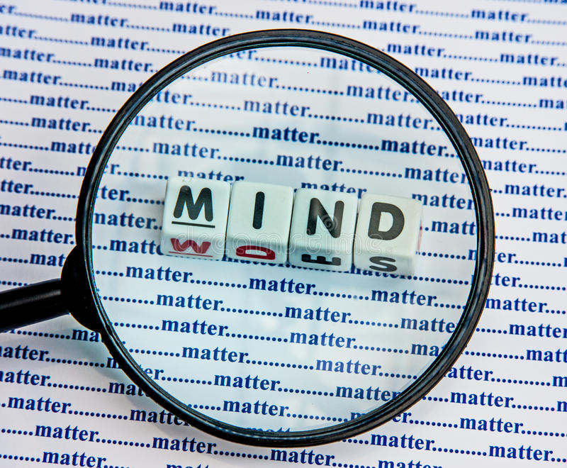 Mind over matter. Text 'mind' in uppercase letters inscribed on small white cubes viewed through a hand magnifier against a background of 'matter' repeated royalty free stock images