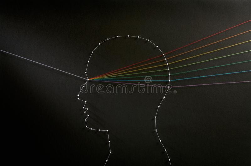 Mind prism. Input output concept. Rainbow mind concept. Network of pins and threads in the shape of a ray of light going through a persons head symbolising that royalty free stock image