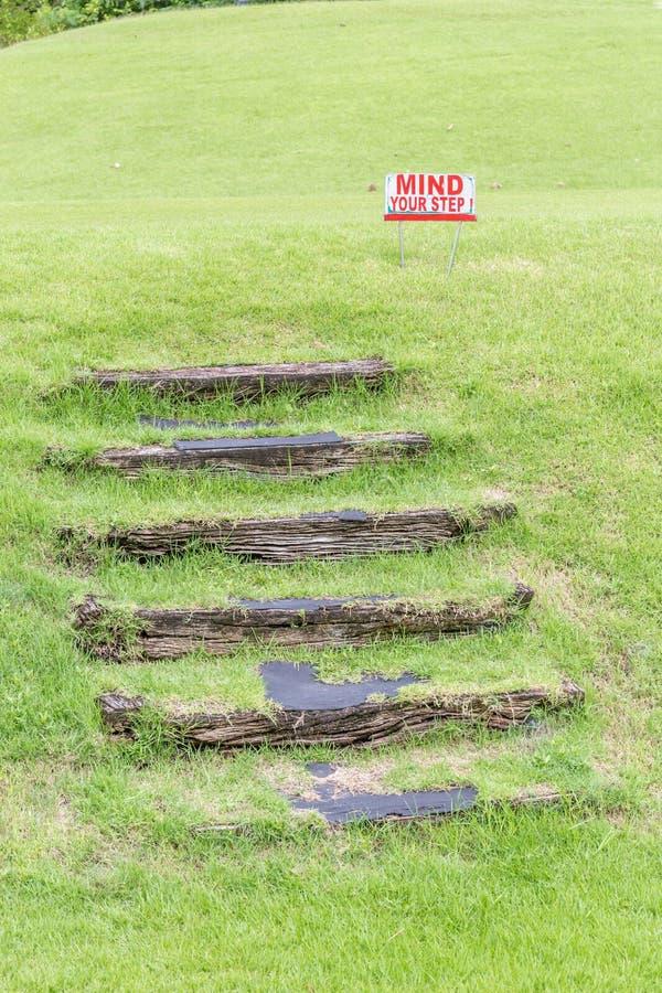 """""""Mind uw step"""" waarschuwingsbord dichtbij natuurlijke houten stappen op g royalty-vrije stock fotografie"""