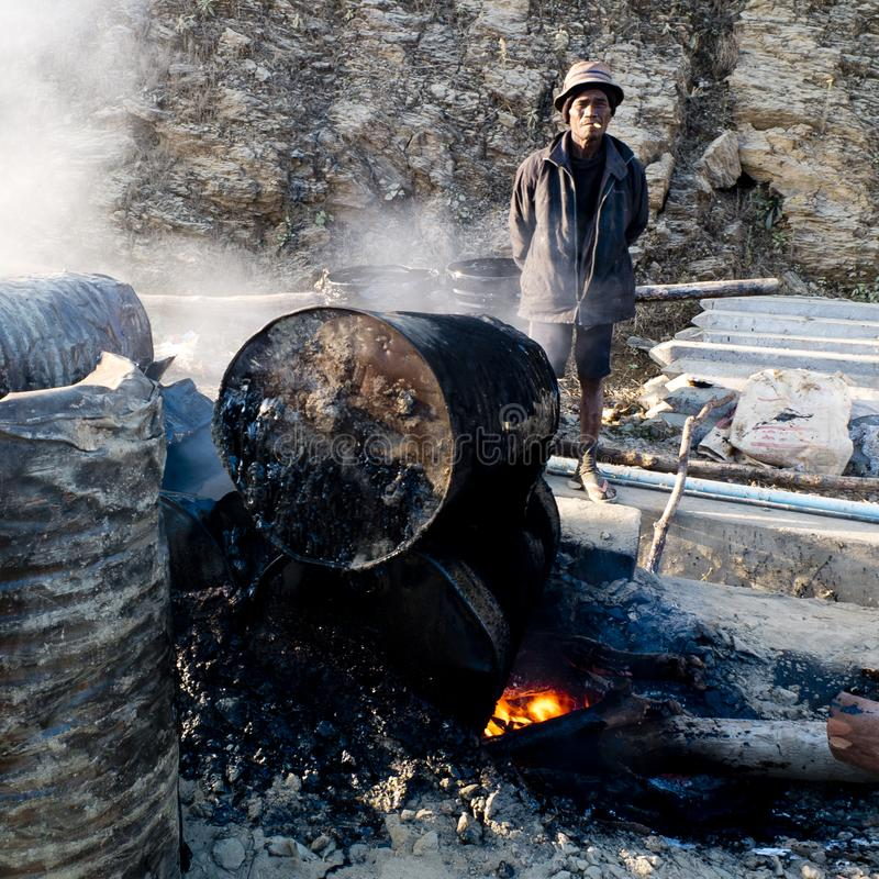 Worker looking after the tar combustion stock image