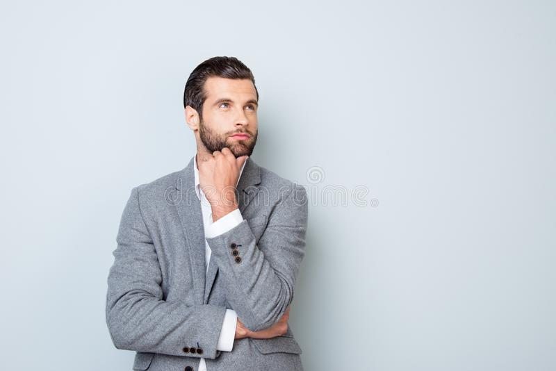 Minded handsome young man planning how to launch a new project isolated on white gray grey background copy-space copyspace thought stock photo