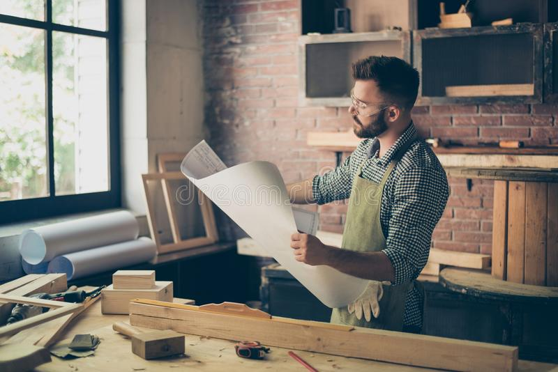Minded pensive thoughtful confident attentive bearded young concentrated wearing checkered shirt and apron handymaster is holding royalty free stock photo