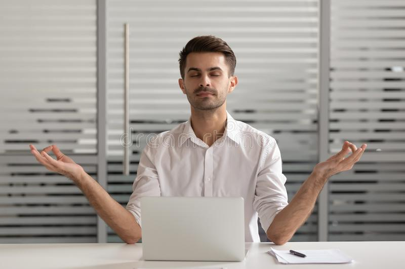 Mindful carefree millennial male manager meditating in office. royalty free stock image