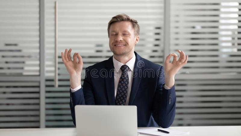 Mindful happy businessman relaxing meditating sit at office desk stock photo