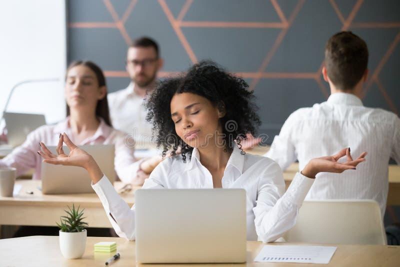 Mindful millennial african woman meditating with colleagues, cor. Mindful millennial african women meditating at workplace with colleagues, calm black employee stock image