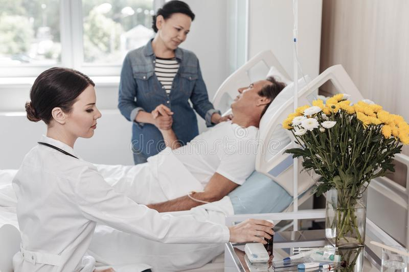 Mindful wife supportive ill husband in hospital stock photography