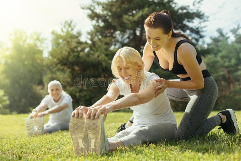Mindful young lady helping retired woman with exercise royalty free stock photos