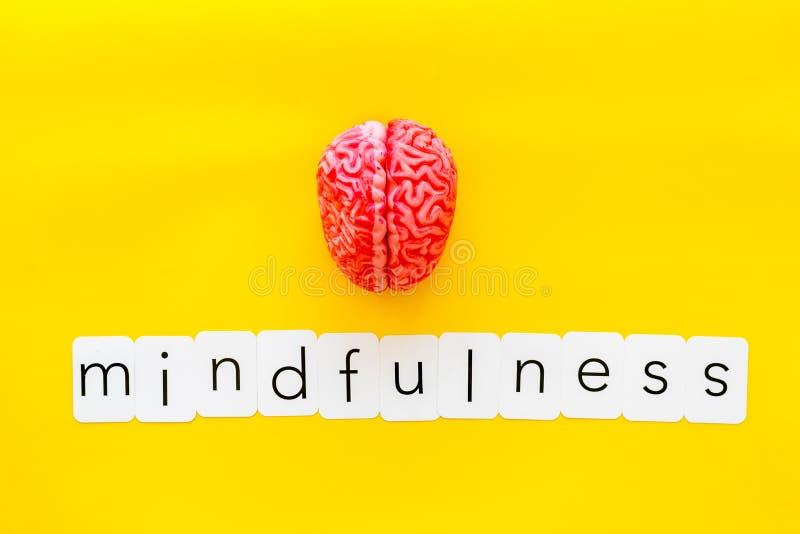 Mindfulness en meditatieconcept met hersenen op gele hoogste mening als achtergrond stock afbeelding
