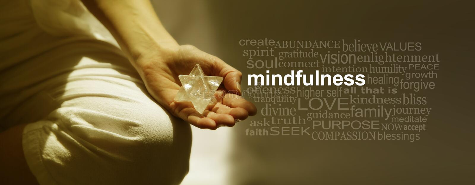 Mindfulness Meditation Word Cloud Banner. Female sitting in Lotus Position on left side with sunlight streaming in holding a Merkabah crystal meditating and a royalty free stock photography