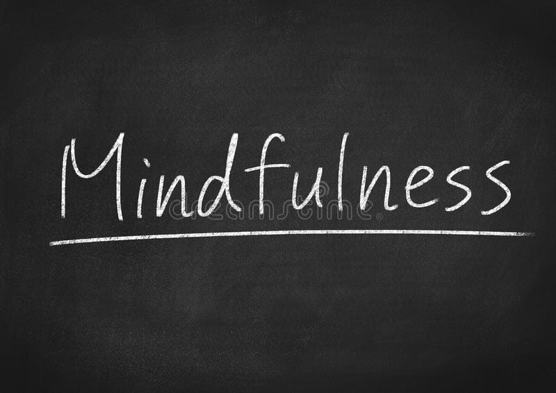 Mindfulness. Concept word on a blackboard background stock photography