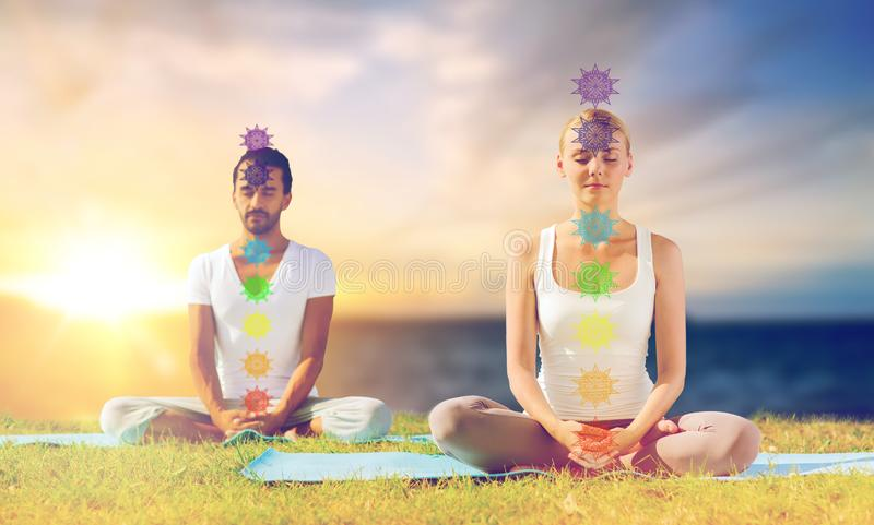 Couple doing yoga in lotus pose with seven chakras royalty free stock photography
