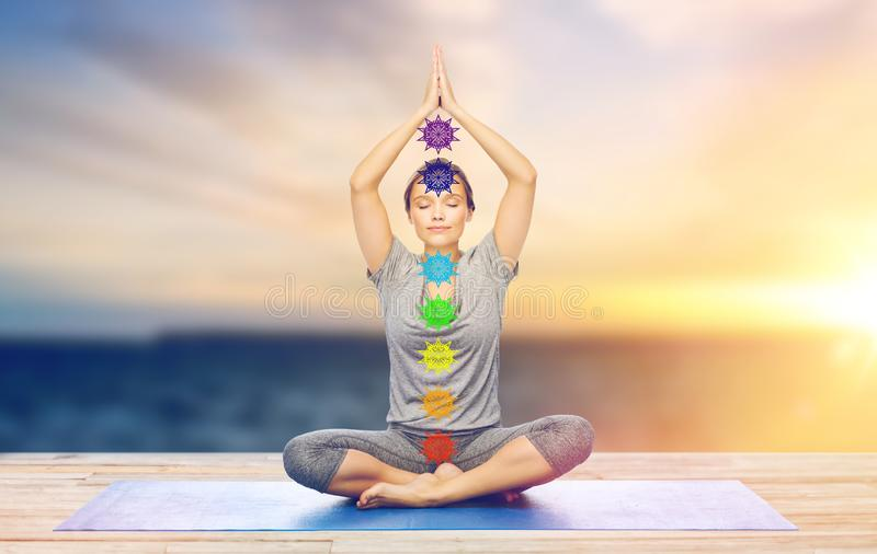 Woman doing yoga in lotus pose with seven chakras royalty free stock photo