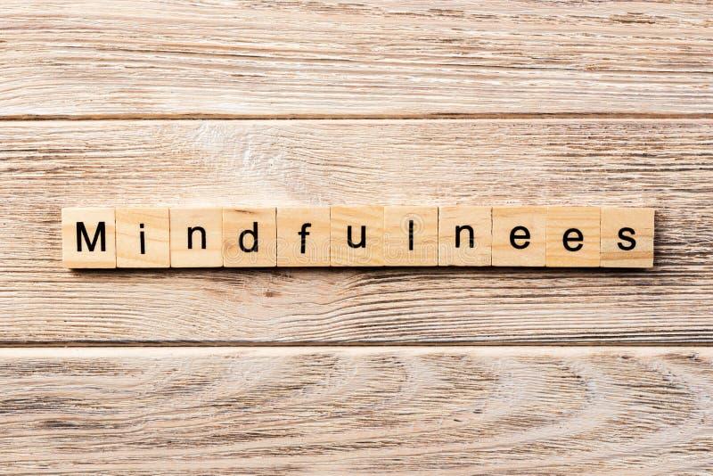 Mindfulnessord som är skriftligt på träsnittet mindfulnesstext på tabellen, begrepp arkivfoton