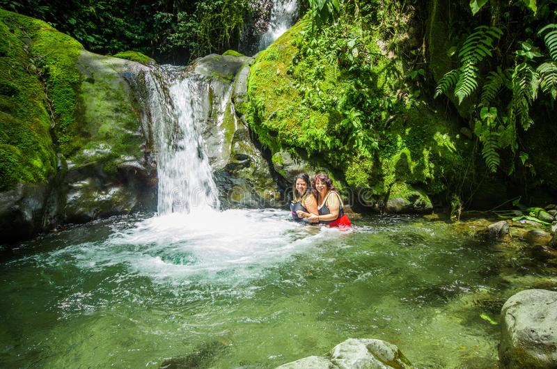 MINDO ECUADOR - AUGUSTI 27, 2017: Oidentifierat folk som nära simmar av den härliga vattenfallet i grön skog med arkivbilder