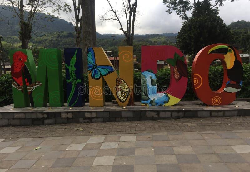 Mindo - Ecuador 1-5-2019 som, är skriftliga i bokstäver och som är pålagda den huvudsakliga plazaen med rainforesten i bakgrunden royaltyfri bild