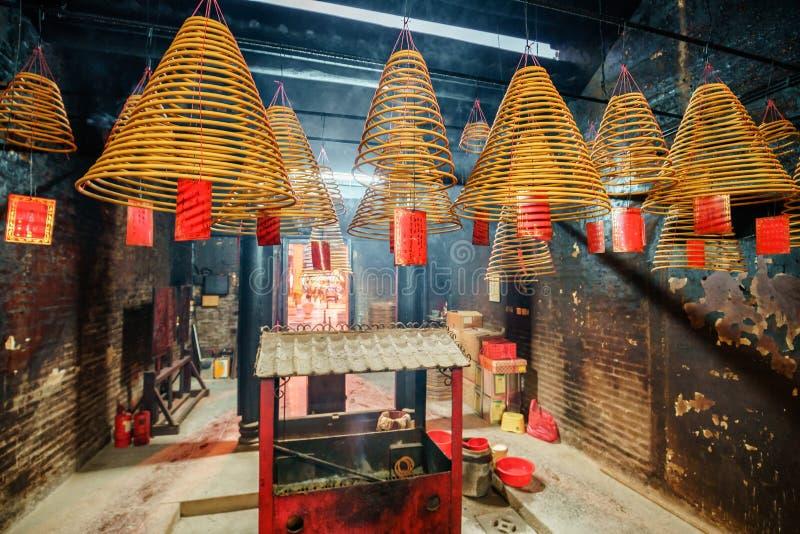 Mindre inre för buddistisk tempel i historisk mitt av Macao Brinnande rökelsebönkottar och en rökelsekar arkivfoto