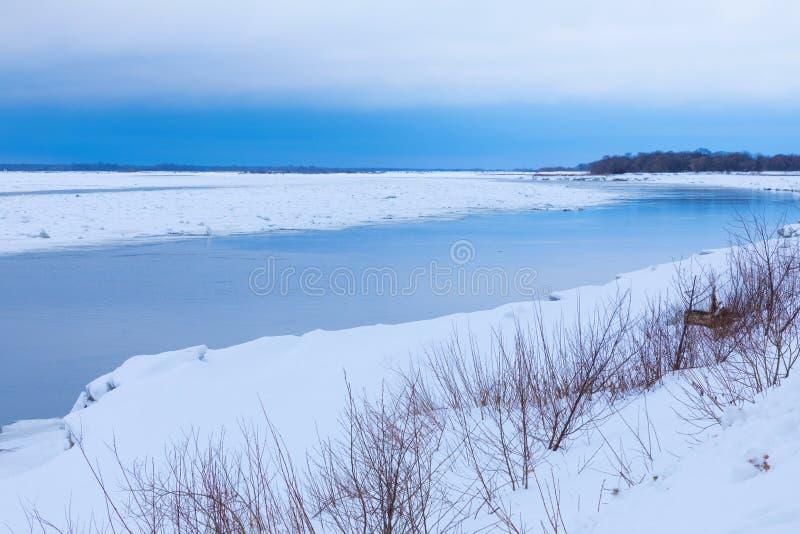 Mindre kulle och isflaken på vinterfloden royaltyfri bild