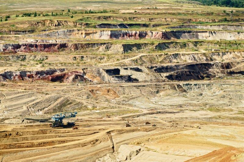 Mine à ciel ouvert de mur de couchette avec les minerais et la lignite colorés exposés, l'équipement minier de mine photographie stock libre de droits