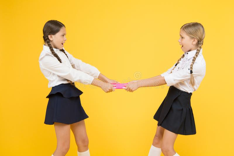 This is mine. girls can`t share a book. kids learning grammar. back to school. Get information. love reading. childrens. Literature. outraged classmates with royalty free stock photography
