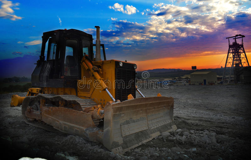 Mine shaft sunrise with earth mover machine. A vertical mine shaft at sunrise with earth mover machine in foreground royalty free stock photo