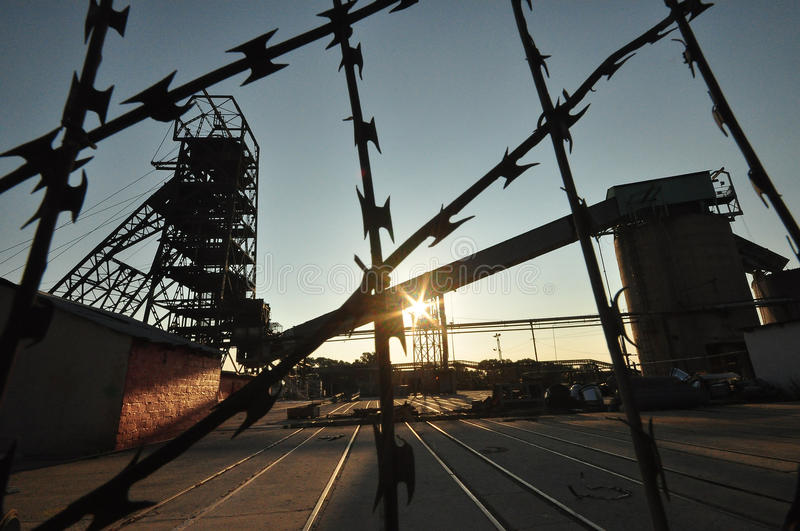 Mine. Silhouetted against the rising sun. Razor wire in the forefront royalty free stock photo