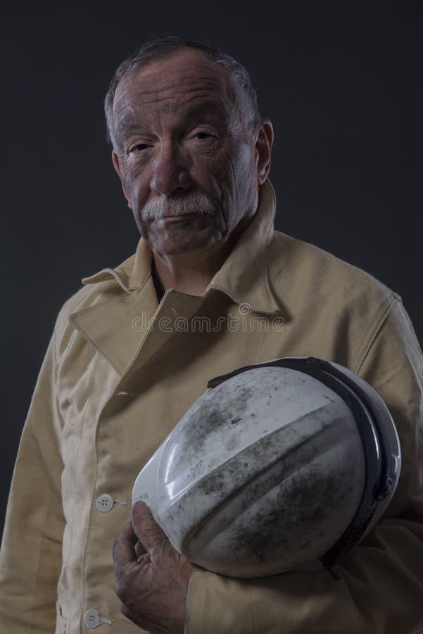 Mineiro maduro coberto na poeira de carvão que guarda um capacete de segurança fotografia de stock royalty free