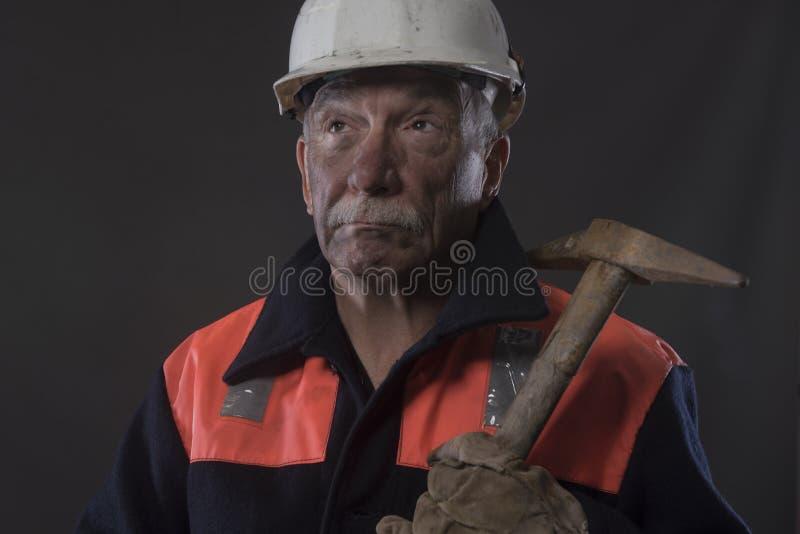 Mineiro maduro coberto na poeira de carvão que guarda uma picareta imagem de stock