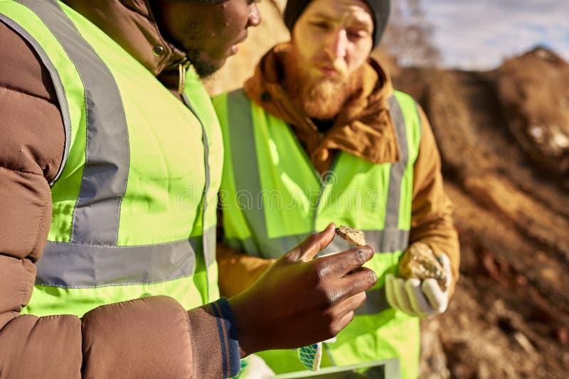 Mineiros que inspecionam a terra para minerais imagens de stock