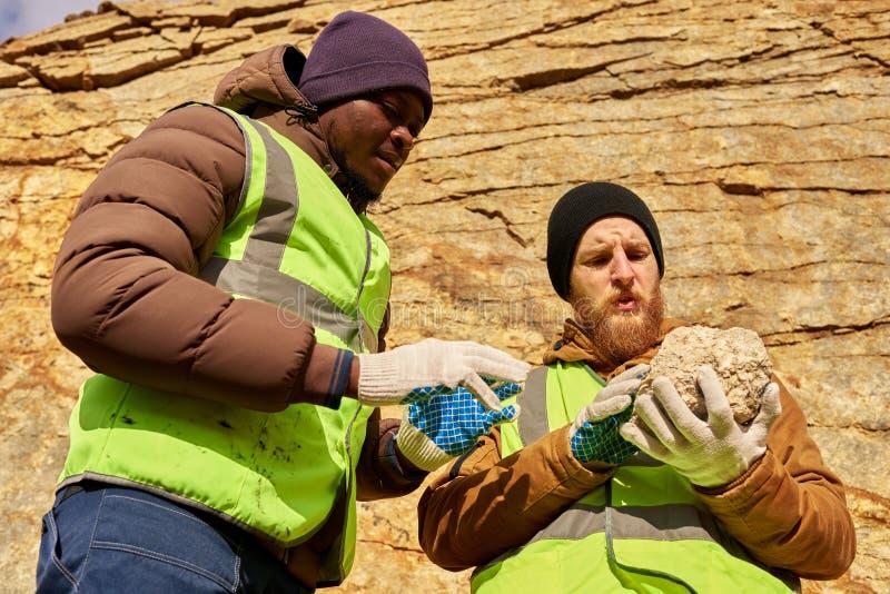 Mineiros que inspecionam a terra que procura por minerais foto de stock